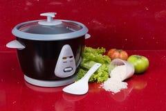 Hervidor de arroz eléctrico, en el rojo de la cocina en hogar moderno Fotos de archivo libres de regalías