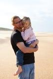 Hervorbringen Sie das Anhalten der Tochter in den Armen am Strand Stockbild