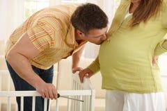 Küssender schwangerer Bauch des Vaters Stockbilder