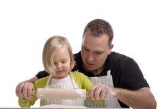Hervorbringen Sie das Lernen seines kleinen Mädchens, wie man einen Kuchen bildet stockbild