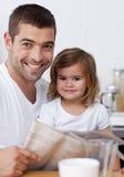 Hervorbringen Sie das Lesen einer Zeitung mit seiner Tochter Stockfotografie