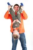 Hervorbringen Sie in der orange Kleidung, die seine Kindoberseite anhält stockbild