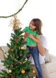 Hervorbringen Sie Holding ihre Tochter für den Weihnachtsbaum Lizenzfreies Stockfoto