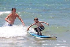 Hervorbringen Sie, seinen jungen Sohn beibringend, wie man surft Stockfotografie