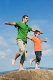 Hervorbringen Sie und sein Sohn, der auf dem Stein bleibt Lizenzfreies Stockfoto