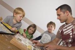 Hervorbringen Sie und seine Kinder, die Plätzchen für Weihnachten schneiden Lizenzfreies Stockfoto