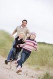 Hervorbringen Sie und zwei junge Kinder, die am Strand laufen Stockbild
