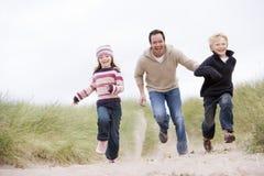 Hervorbringen Sie und zwei junge Kinder, die am Strand laufen lizenzfreies stockfoto
