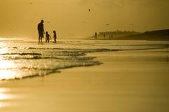 Hervorbringen Sie und zwei Kinder, die auf dem Strand spielen