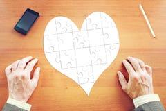 Herz als gesammelte Puzzlespiele auf dem Schreibtisch Lizenzfreie Stockfotos