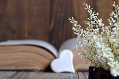 Herz, altes Buch und Blumen stockbild