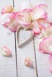 Herz auf Blumenblättern auf hölzernem Hintergrund Stockfotografie