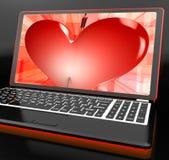 Herz auf dem Laptop, der Amor-Schuss zeigt Stockbild