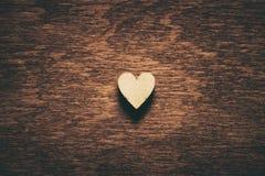 Herz auf dunklem hölzernem Hintergrund Stockfotografie