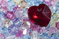 Herz auf kleinen Glasperlen Stockbild