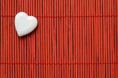 Herz auf roter Bambusoberer linker ecke stockfotografie