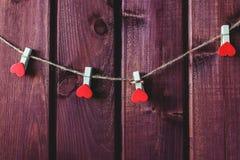Herz auf Schnur mit hölzernem Hintergrund Stockfoto