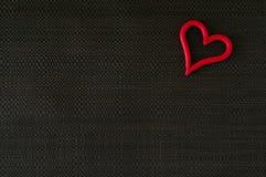 Herz auf schwarzem Gewebe Stockfoto