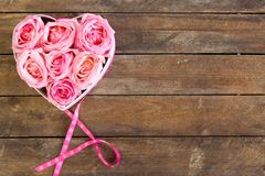 Heart of roses in pink with ribbon on wooden background stock photos