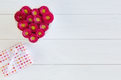 Heart from red Bellis and gift box with bow on wooden background in white stock image