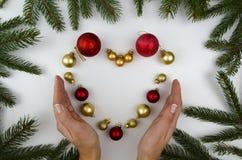 Herz ausgemacht von den Weihnachtsdekorationen und von woomen Händen Weiße Hintergrundweihnachtsbälle Flache Lage Lizenzfreies Stockfoto