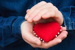 Herz in den Händen eines Mannes Stockfoto