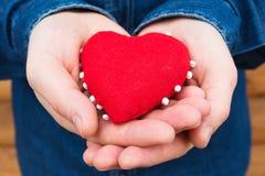 Herz in den Händen eines Mannes Stockfotografie