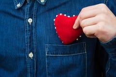 Herz in den Händen eines Mannes Stockbild
