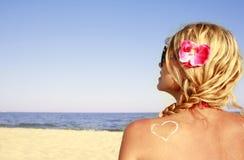 Herz der Creme auf der Fraurückseite auf dem Strand Stockfoto