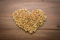 Herz der Erdnuss über HÖLZERNEM Hintergrund Stockbilder