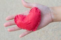 Herz der Erschließung des Papiers an Hand einer jungen Frau Zeigen von Liebe stockfoto