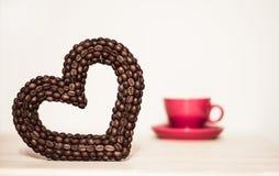 Herz der Kaffeebohnen und der roten oder rosa Schale Zwei verklemmte Innere Seien Sie mein Valentinsgruß Lizenzfreie Stockbilder