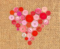 Herz der roten Knöpfe auf Sacksegeltuch-Leinwandhintergrund Lizenzfreie Stockbilder