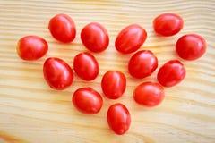 Herz der Tomate in Form auf hölzerner Platte Stockfotos