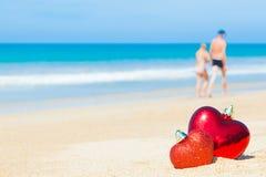 Herz des Bonbons zwei auf Zusammenfassungshintergrundliebe des blauen Himmels des Sandstrandes Lizenzfreie Stockfotografie