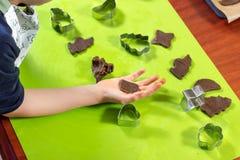 Herz des Kuchens liegt auf der Kinderhand Die Metallformen liegen unter heraus zusammengedrückt formt von einem braunen Teig auf  stockfotografie