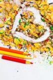 Herz, drei Bleistifte und farbige hölzerne Schnitzel Lizenzfreie Stockbilder