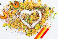 Herz, drei Bleistifte und hölzerne Schnitzel Stockfotos