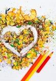 Herz, drei Bleistifte und varicolored hölzerne Schnitzel Lizenzfreie Stockfotos