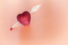Herz durchbohrt durch einen Pfeil auf rosa Hintergrund Symbolisches Blut dri Lizenzfreie Stockfotografie