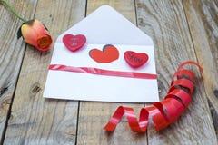 Herz in einem weißen Umschlag und in einer Rose Stockfotos