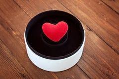 Herz in einer runden Geschenkbox auf einem hölzernen Hintergrund Lizenzfreies Stockfoto