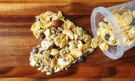 Herz-förmig von den Corn-Flakes mit Mandel, Honig, indischem Sesam und Trockenfrüchten Lizenzfreie Stockbilder