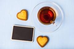 Herz-förmige Kekse und Tee stockbilder