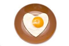 Herz-förmiger Fried Egg auf Brown-Platte Lizenzfreie Stockbilder