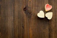 Herz-förmiger Konfektionsartikel für Valentinstag auf dunklem hölzernem Draufsicht-Kopienraum des Hintergrundes stockfotografie