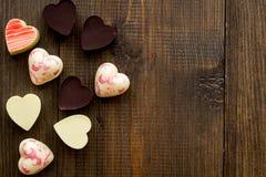 Herz-förmiger Konfektionsartikel für Valentinstag auf dunklem hölzernem Draufsicht-Kopienraum des Hintergrundes stockfotos