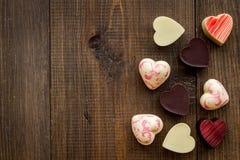 Herz-förmiger Konfektionsartikel für Valentinstag auf dunklem hölzernem Draufsicht-Kopienraum des Hintergrundes stockbild