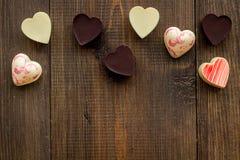 Herz-förmiger Konfektionsartikel für Valentinstag auf dunklem hölzernem Draufsichtraum des Hintergrundes für Text stockbilder