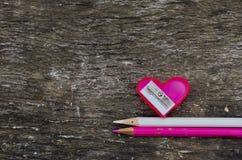 Herz-förmiger rosa Bleistiftspitzer und zwei Bleistifte Stockbild
